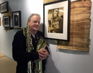Danny Harrington with Harry Carney's horn, standing in front of a photo of Pat Patrick